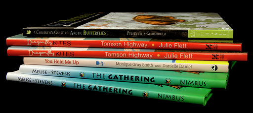 Colour photograph of six books placed in a stack.