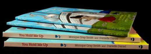Colour photograph of four books placed in a stack.