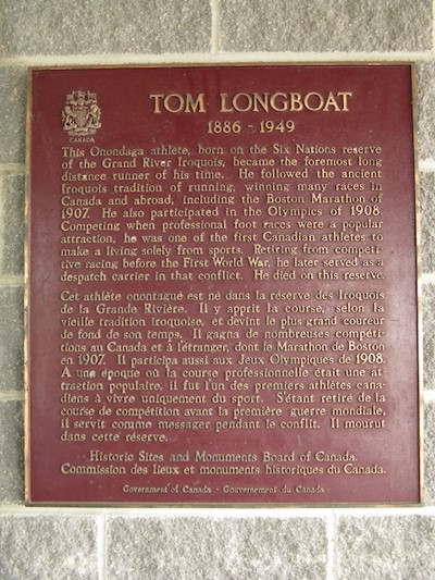 "A red rectangle plaque with gold writing, with the crest of Canada and ""Tom Longboat 1886–1949"" at the top."