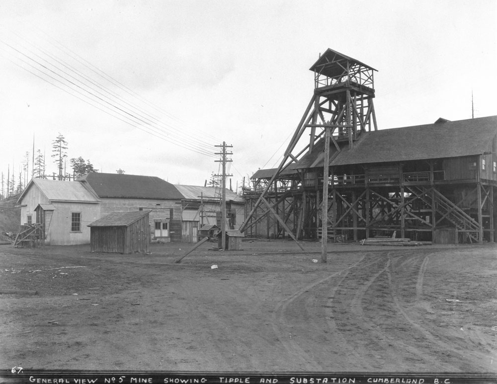 Black and white photograph of a mine. On the right is a sub-station and a wood-frame tipple used to load the coal extracted for transport. On the left are closed buildings. Overhead wires connect the buildings in the foreground.