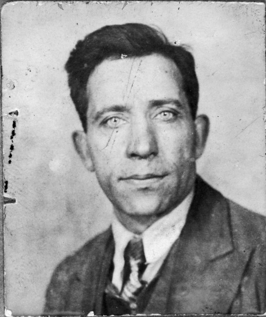 A black and white photograph of a man in a suit and tie staring towards the camera.