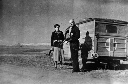 A black and white photograph of a man and a woman standing in front of a truck whose back is marked with a white cross.