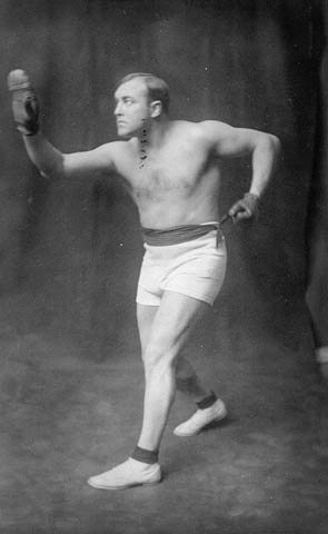 Black-and-white photo of a man wearing boxing gloves, shorts and shoes.