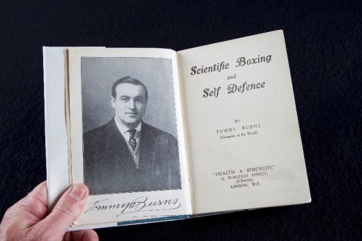 Black-and-white photo of a hand holding a book open at the title page.