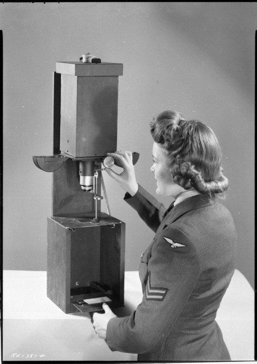 Black-and-white photo of a woman in military uniform using an enlarger.