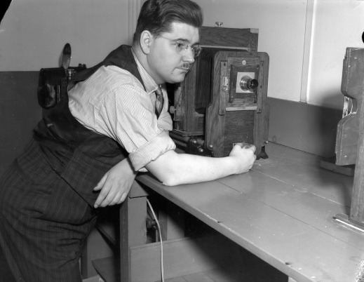 Black-and-white photo of a man leaning on a desk next to an enlarger.