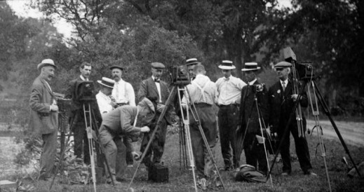 Black-and-white photographers belonging to Toronto's Camera Club posing outdoors with their camera equipment.