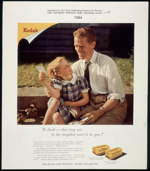 "A man in a shirt and tie sitting with a young girl in a plaid dress, smiling and looking at a photograph. The brand name ""Kodak"" appears in the top left-hand corner."