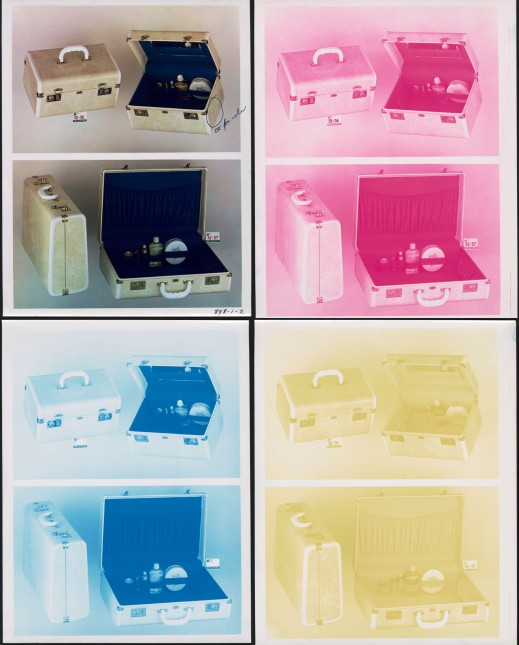 Colour photograph of a carrying case and three identical negatives, each in a different colour: magenta, cyan, and yellow.