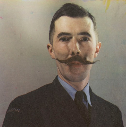 A colour portrait photograph of Brodie Macpherson in a military uniform sporting a handlebar moustache. The figure is cropped at the chest and appears against a blank background.