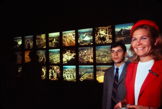 In the background is a grid of backlit colour transparencies of aerial shots. In the foreground are a Kodak representative and a male figure.