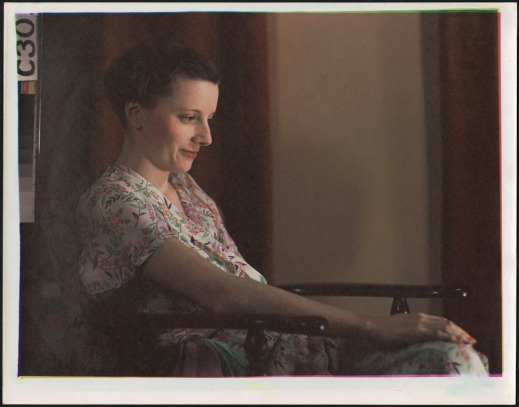 Colour portrait of a woman in a floral dress, front lit, seated in a wooden armchair.