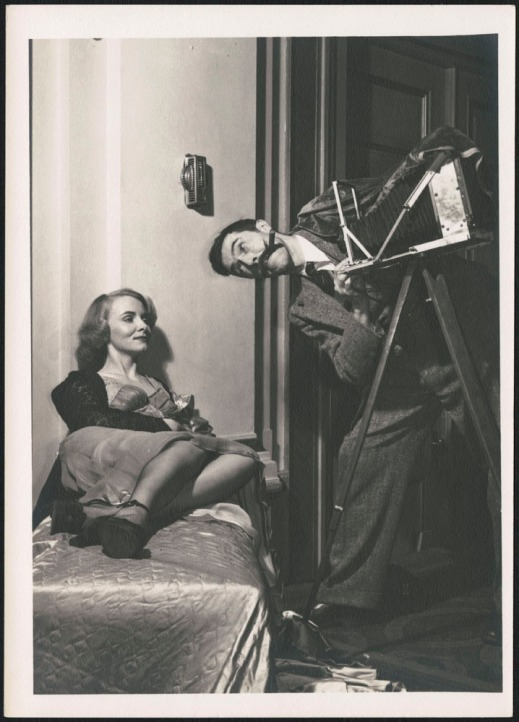 A black-and-white photograph of Brodie Macpherson pretending to photograph a reclined Miss 1948, Lialla Raymes.
