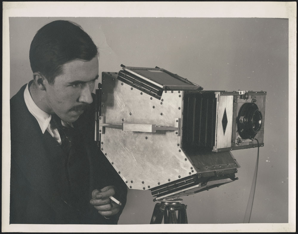 A black-and-white photograph of Brodie Macpherson using his Devin-style one-shot camera.