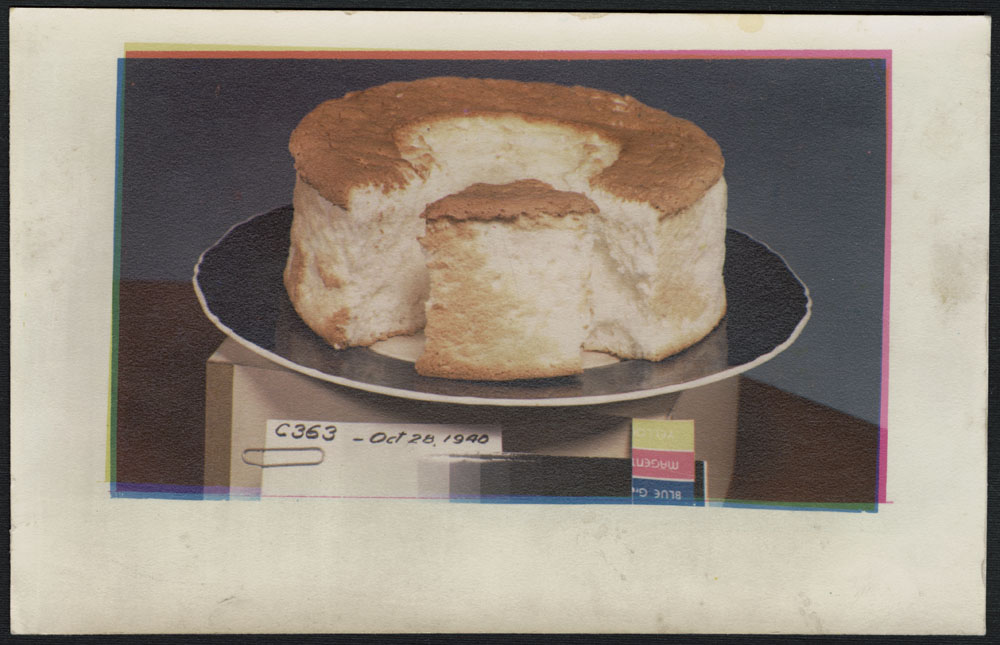 A print of a cut round cake on a black plate, situated atop a box bearing the printing matrix and creator number C363.