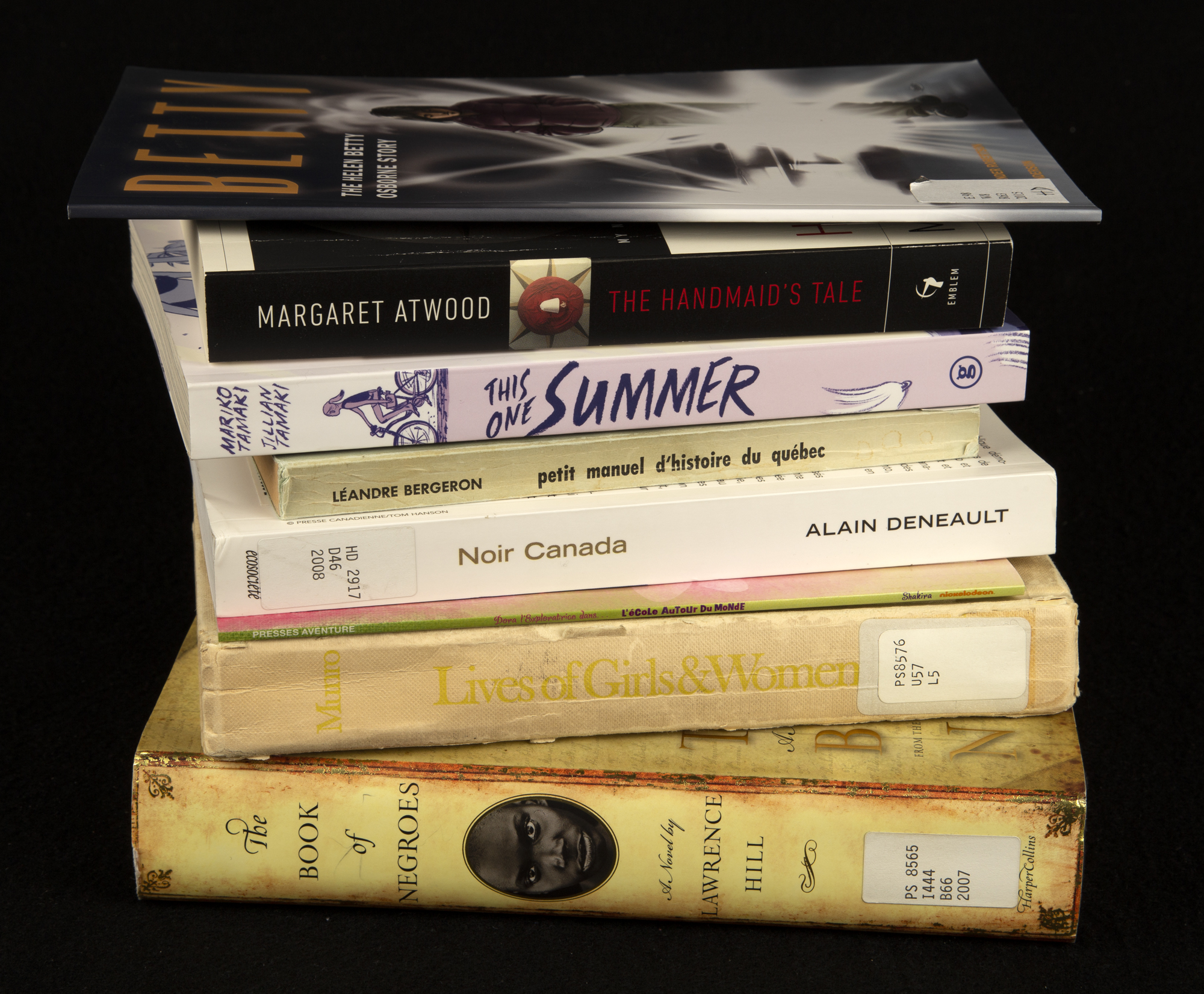 A colour photograph showing the spines of a stack of books against a black background.