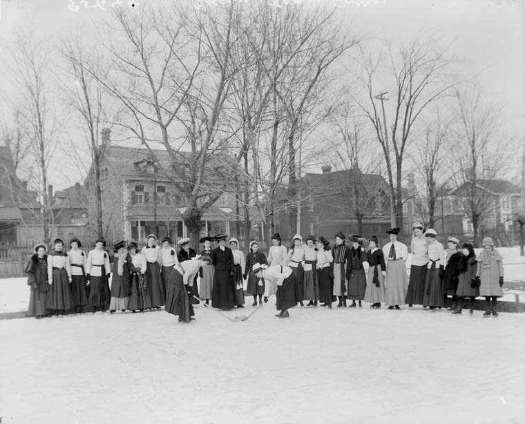 A black and white photo taken outside with women in long skirts.