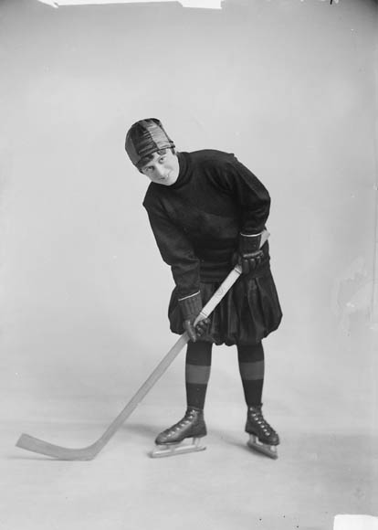 A black and white photo of a woman as a professional hockey player.