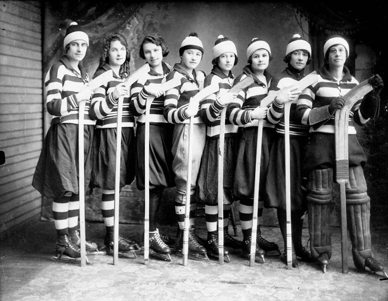 A black and white photo of a women's hockey team lined up with the butt end of their sticks on the ground and dressed in their team uniform.