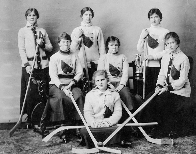 A black and white photo of a women's hockey team. The women have team sweaters on and are holding their hockey sticks.