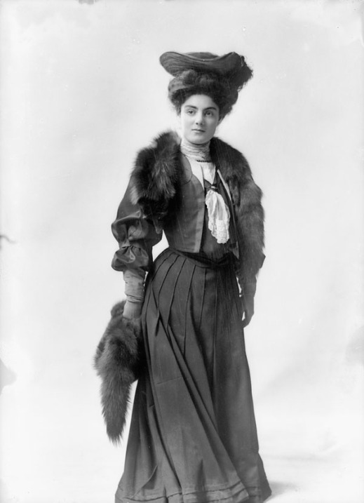 Black-and-white photo of a woman standing and facing the camera, wearing a dark-coloured dress, a fancy hat and a fur stole.