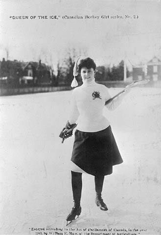A black and white photo of a woman dressed in a skirt to play hockey outside.