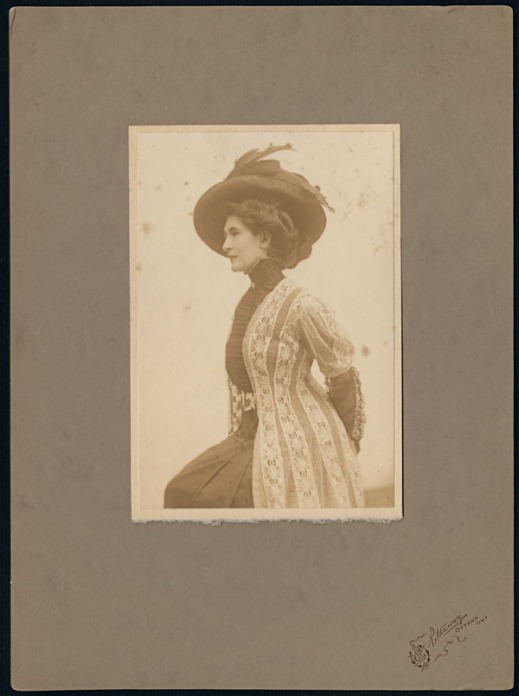 Side profile of Madge Macbeth in a black dress and white lace jacket wearing a feathered hat.