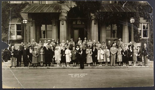 Large group of men and women standing in front of the entrance to a building.