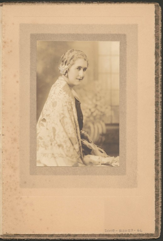 Side portrait of Madge Macbeth wearing a pale patterned cape.