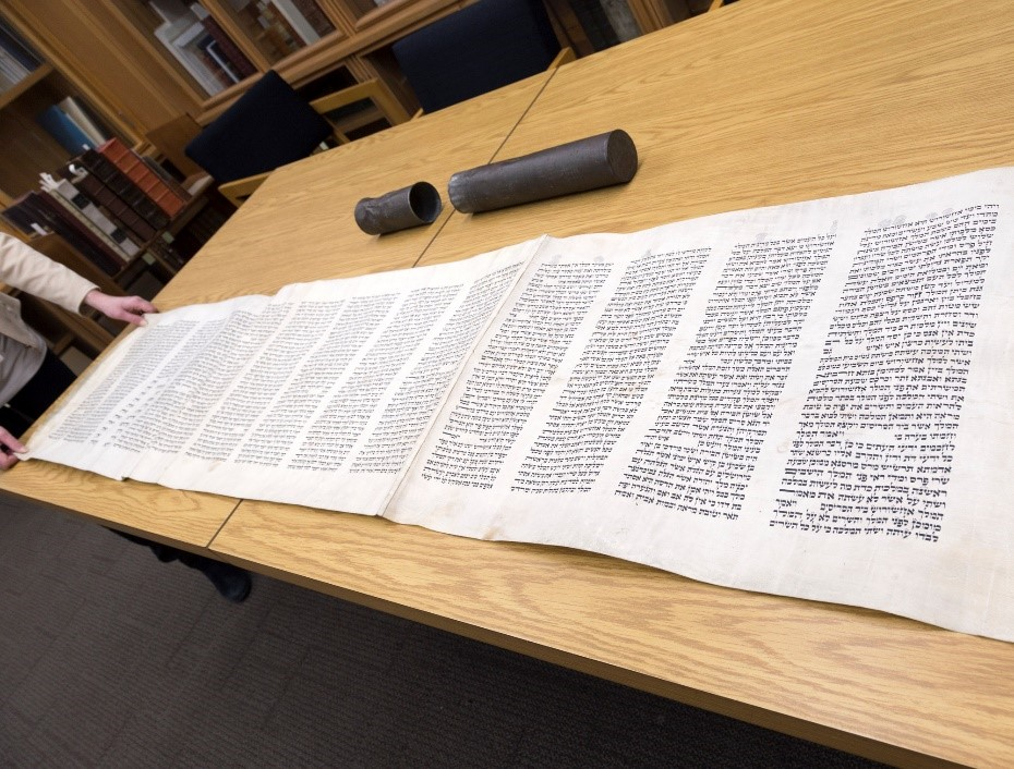 A colour photograph of a handwritten Hebrew manuscript on parchment completely rolled out across a table, approximately seven feet in length. Also on the table is the protective metal casing that originally housed the manuscript.