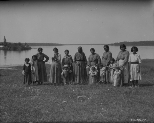 A black-and-white photograph of 7 women, a teenager and children on the shore of a lake. Two babies are in cradleboards.
