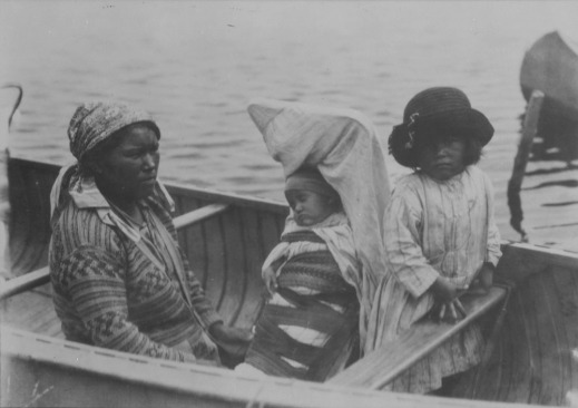 A black-and-white photograph of a woman and two children in a canoe. One of the children is sleeping in a cradleboard.