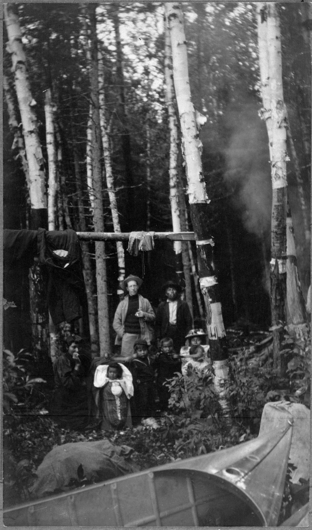A black-and-white photograph of eight people, including a baby in a cradleboard in a forest. There is a canoe in the foreground.