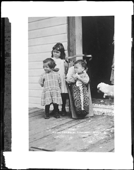 A black-and-white photograph of three children. The youngest child is in a cradleboard that is embroidered with a pattern of flowers.