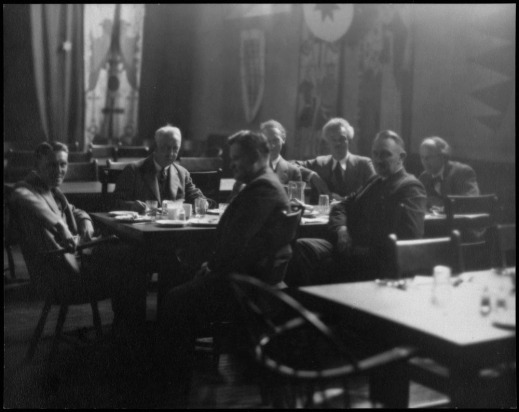 A black-and-white photo of a group of men in suits seated around a table during a meal.