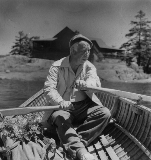A black-and-white photo of a man rowing a wooden boat.