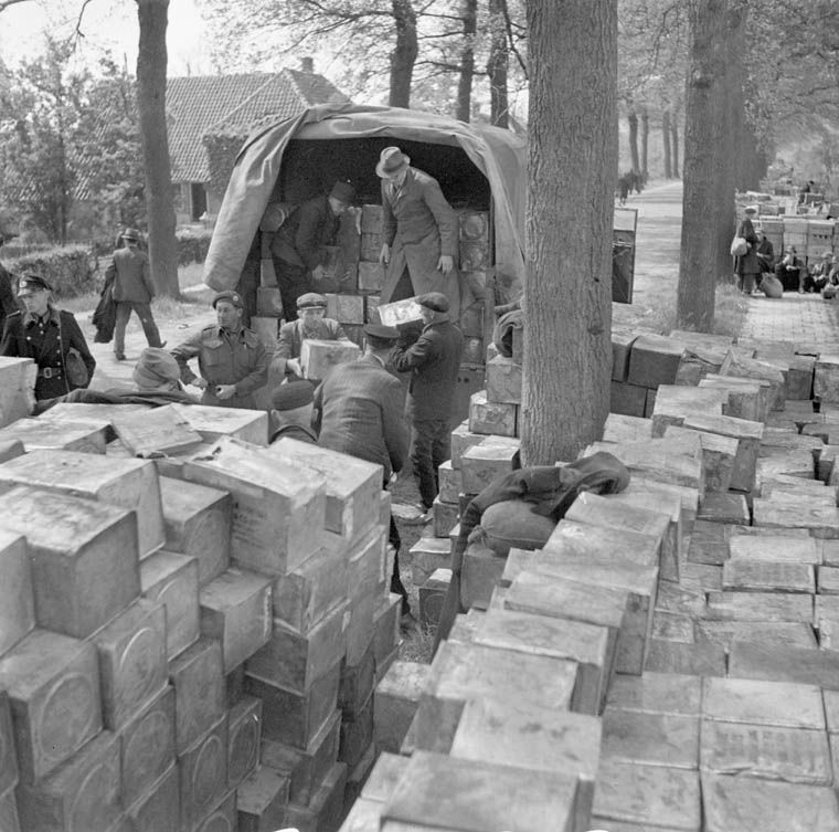 Several people unload food crates from the back of a military truck. Many crates are stacked in the foreground.