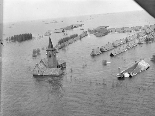 Flooded village with rooftops and a church steeple protruding from the waters.