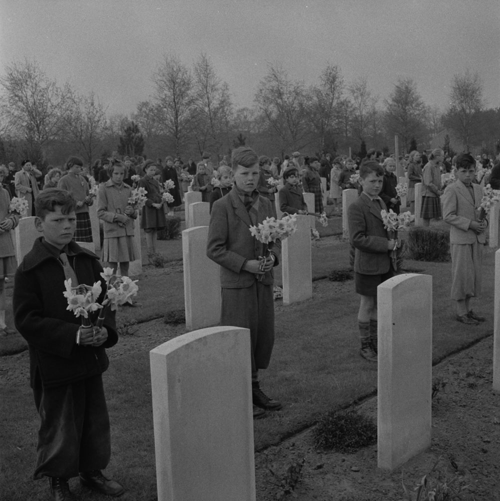 Several children standing in front of headstones, holding bouquets of daffodils.