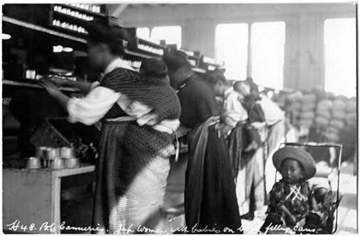 A black-and-white photograph of a factory interior with four women working in a production line on a fish-canning machine. Two of the women have babies strapped to their back with wraps. There is a young child in a stroller behind the women.