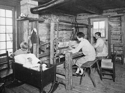 A black-and-white photograph of two women seated on benches in a log cabin. They are working at a large weaving frame while a small child rocks a baby in a cradle nearby.