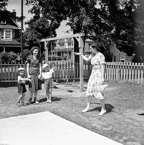 A black-and-white photograph of a mother waving goodbye to her two small children. The children are holding the hands of a daycare worker. The day nursery appears to be in a fenced yard in a residential neighbourhood. There is a swing set in the background.