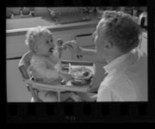 A father spoons food into the mouth of his child, who is seated in a high chair in the kitchen. The father's mouth is open, as he mimics his baby.