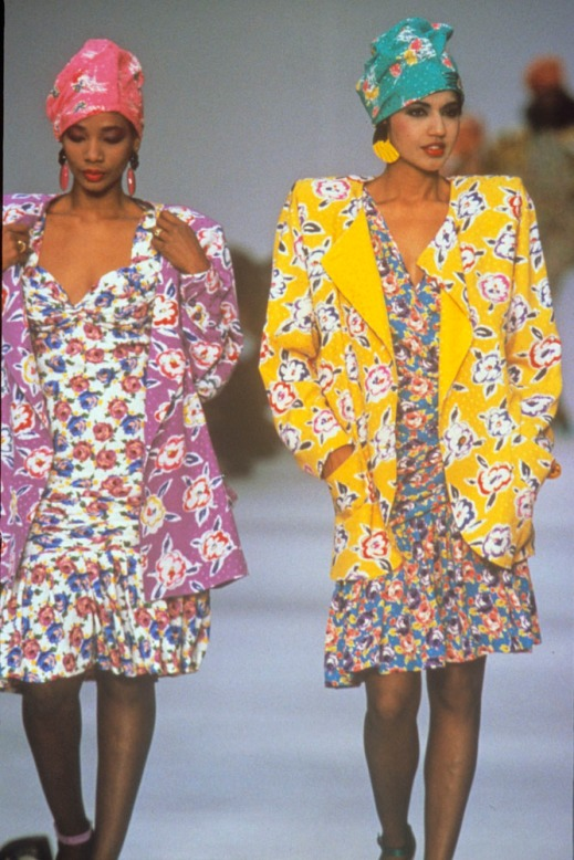 A colour photograph of two women wearing patterned cotton dresses, jackets and headscarves, walking on a runway.