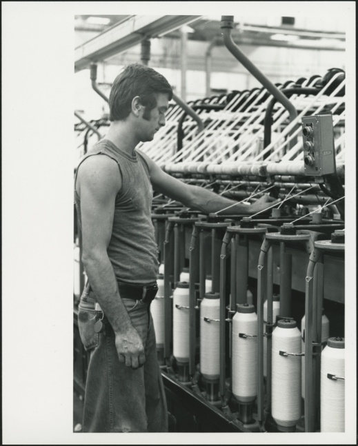 A black-and-white photograph of a man wearing jeans and a sleeveless T-shirt monitoring a spooling machine.