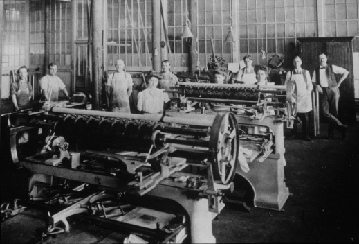 A black-and-white photograph showing men and women posed in a factory with large machines in the foreground.
