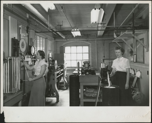 A black-and-white photograph of two women standing and operating devices in a laboratory, with machinery and a large window in the background, and pipes and fluorescent lighting overhead.