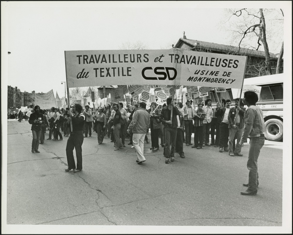 "A black-and-white photograph of a group of people marching in the street, carrying a banner that reads ""Travailleurs et Travailleuses du Textile, CSD [Centrale des syndicats démocratiques], Usine de Montmorency"" [Textile workers, CSD (Congress of Democratic Trade Unions), Montmorency factory]."