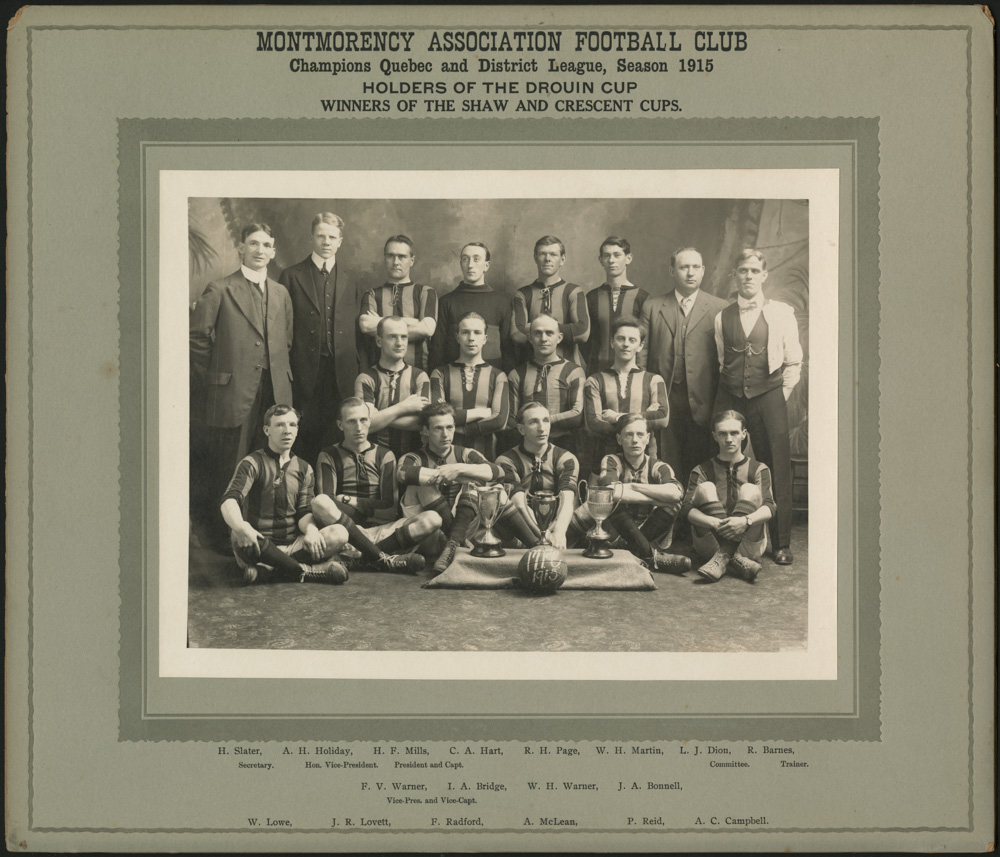A black-and-white matted photograph of a soccer team, with the players in striped jerseys and the coaches in suits.