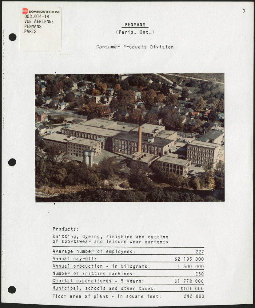 A page from a binder featuring a colour aerial photograph of a factory with a chimney near the centre, surrounded by trees and a town, with statistics below the photograph.